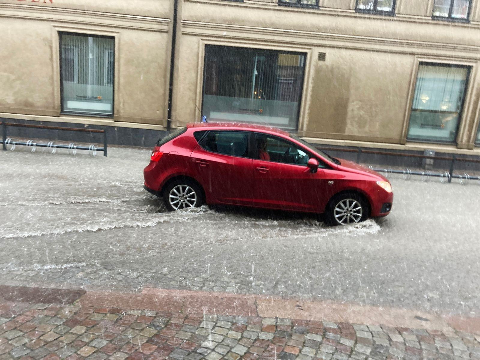 Bil kör genom vattnet på Västra Sjögatan.