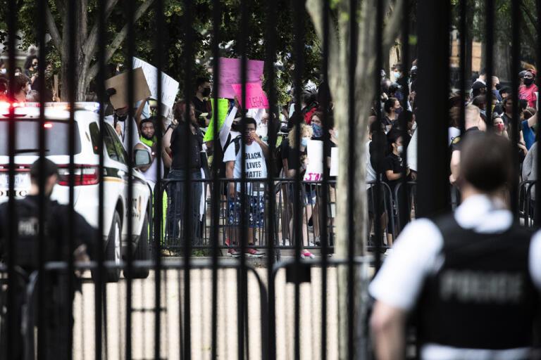 Säkerhetsvakter står utanför Vita huset i Washington på fredagen medan demonstranter protesterar utanför grindarna.