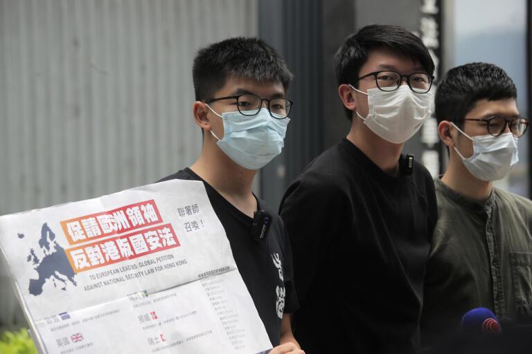 Demokratiaktivisterna Joshua Wong (till vänster), Sunny Cheung (mitten) och Nathan Law med ett plakat som uppmanar europeiska ledare att ta strid mot Kinas planer på att beskära Hongkongs autonomi genom en ny nationell säkerhetslag.