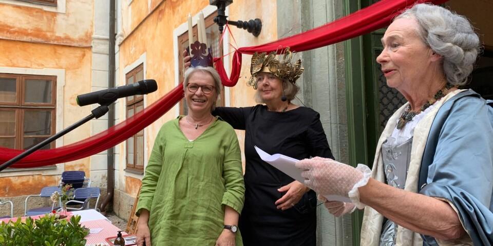 Kafferepets konferencier Boel Marie Larsson sätter kronan på årets Christinapristagare Maria Persson, medan fjolårets pristagare Bodil Mårtensson håller ett hyllningstal.