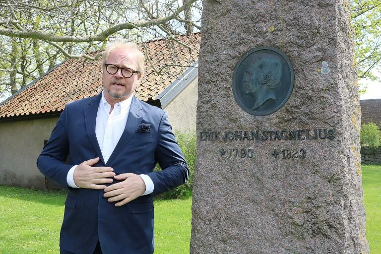 """""""En något förskönad bild av Stagnelius"""", säger Fredrik Lindström där han står framför minnesstenen som Ölandsbladet gjorde en insamling till i början av 1900-talet och som står i trädgården vid Gärdslösa prästgård."""