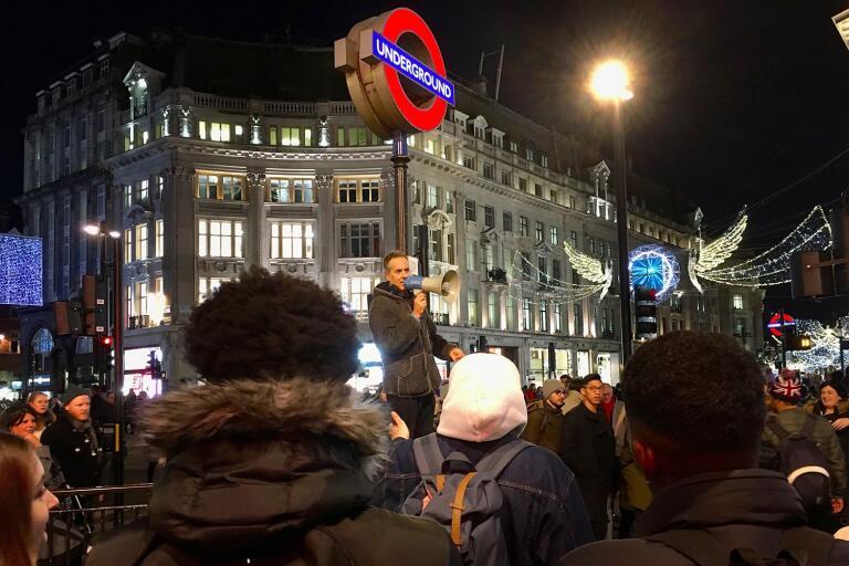 Danny Shine, partiledare för The Expiry Party, drar igång debatten med julshopparna på Oxford Street.
