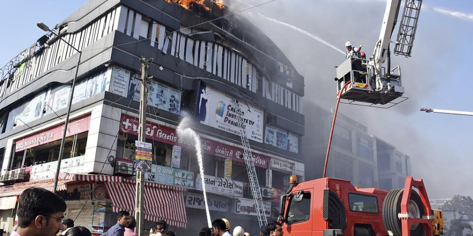 Räddningstjänsten bekämpar elden i flervåningshuset i Surat i västra Indien.