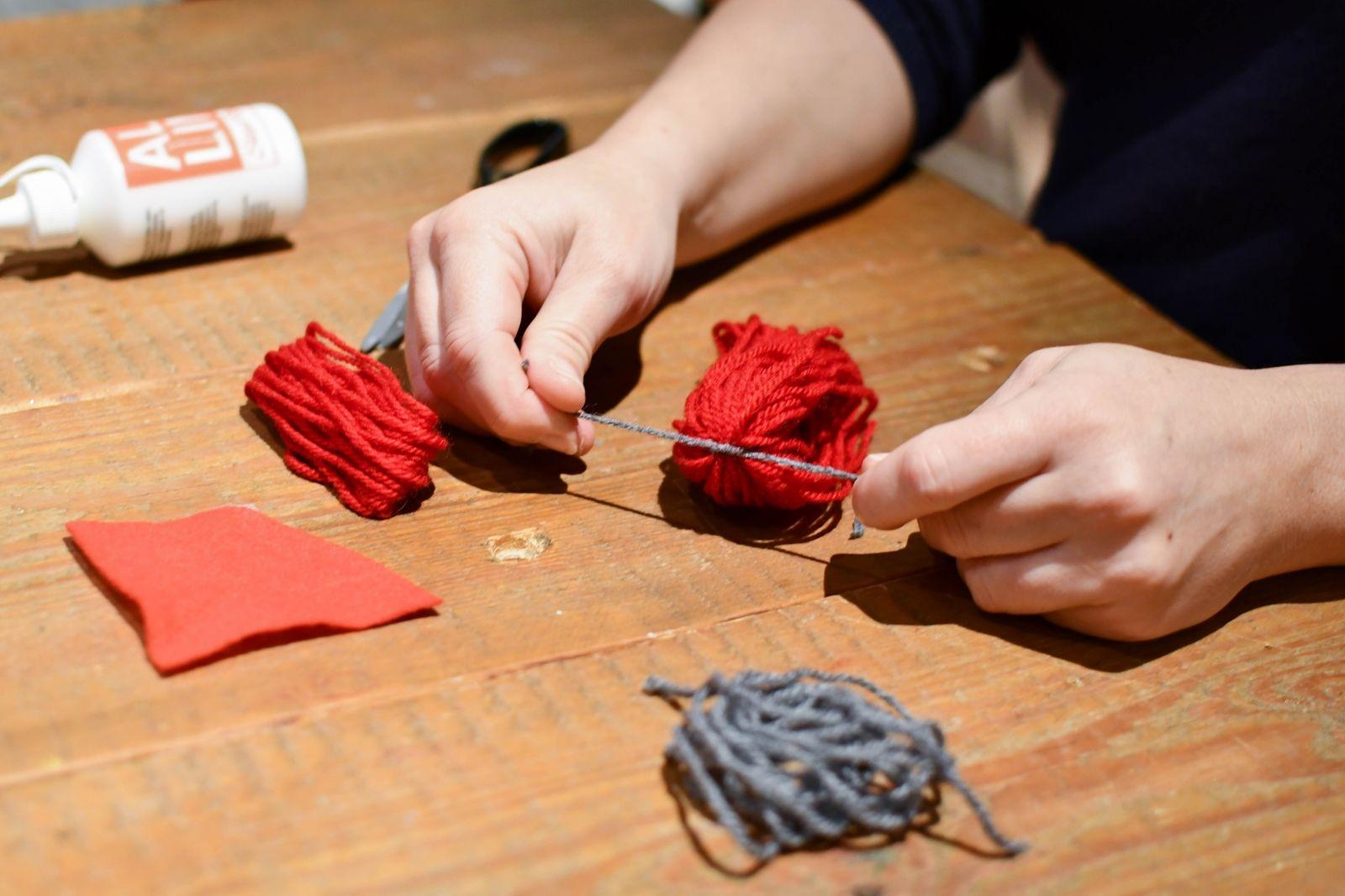 Lossa garnhärvorna försiktigt från kartongbiten som du lindat dem kring. Knyt ihop toppen av den längsta garnhärvan med en bit tråd.
