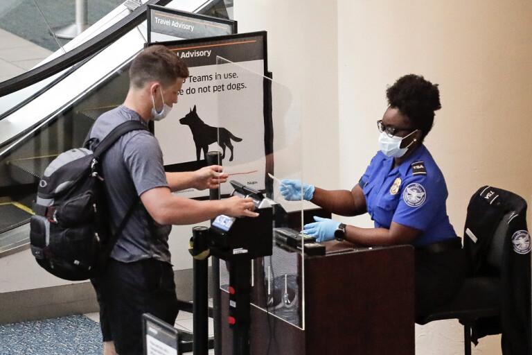 En flygplatsanställd kontrollerar passagerare vid Orlandos flygplats. Arkivbild.
