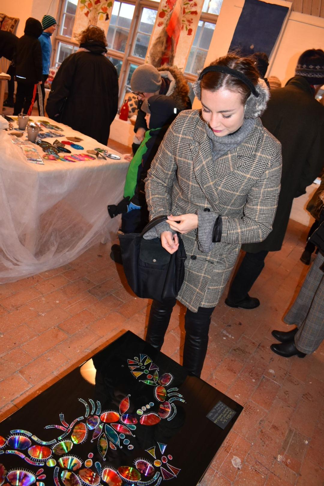 Nathalie Rimsberg beundrar ett annorlunda bord dekorerat med färglagda cd skivor som skapats av Ana Gaines.