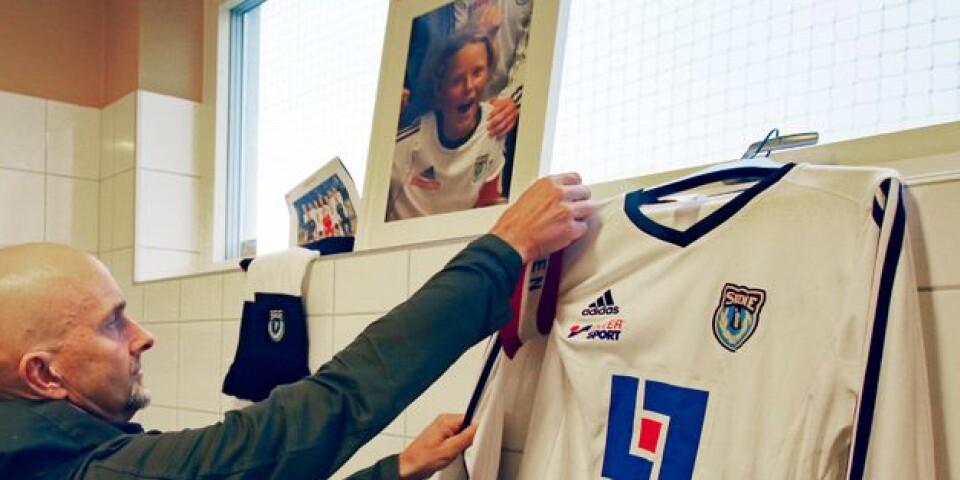 Pappa Mats Olsson ser till att kaptensbindeln sitter rätt på Hugos tröja, där den hänger i ett av Skene IF:s omklädningsrum på Vävarevallen.