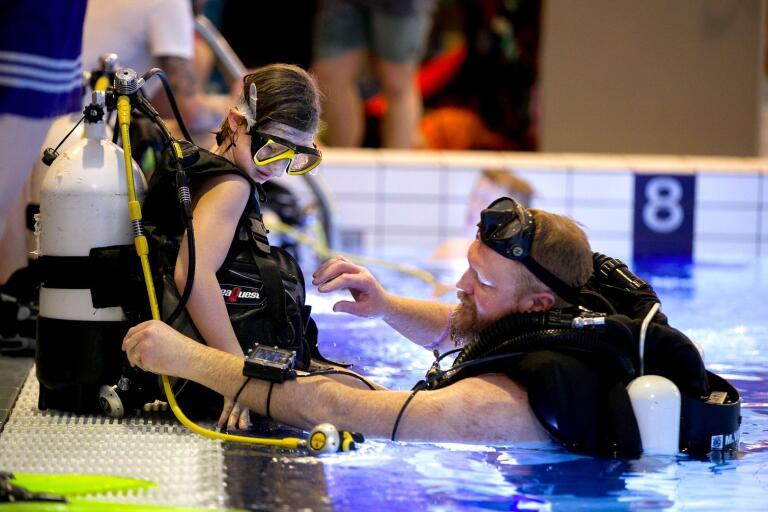 Jasmin Hallberg får hjälp av dykaren Magnus Viklund innan det är dags att prova på att dyka med tub.