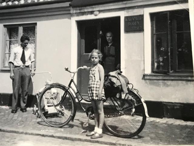 Anna Holm i dörren till Karamellboden. Vid cykeln står Lilian, till vänster på bilden står Gustav och i vagnen sitter sonen Anders.