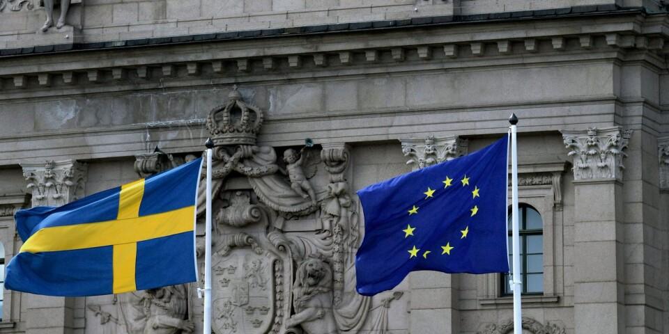 Riksdagshuset med svenska flaggan och EU-flaggan. Men EU ska låta bli den svenska modellen som fungerar bra utan inblandning utifrån.
