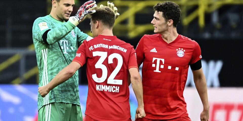Bayern Münchens Joshua Kimmich, mitten, kramas om efter att lobbat in segermålet borta mot Dortmund.