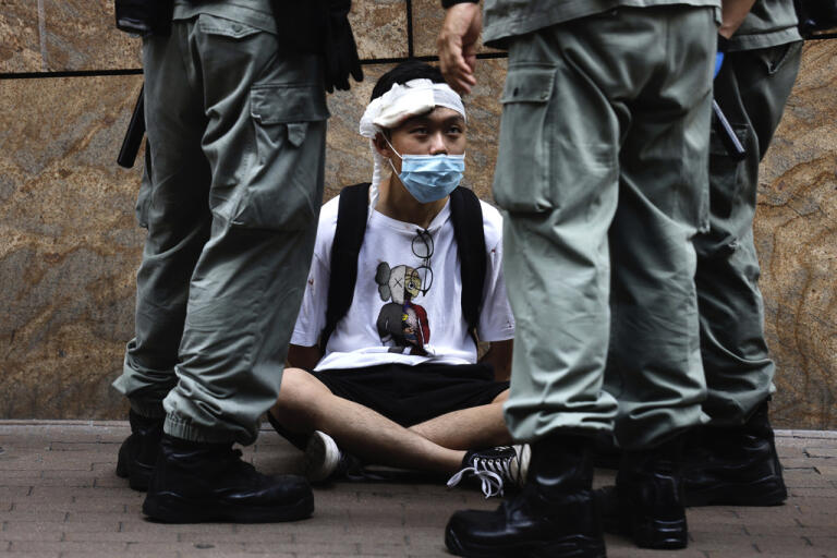 Polis runt en demonstrant i stadsdelen Central i Hongkong på onsdagen.