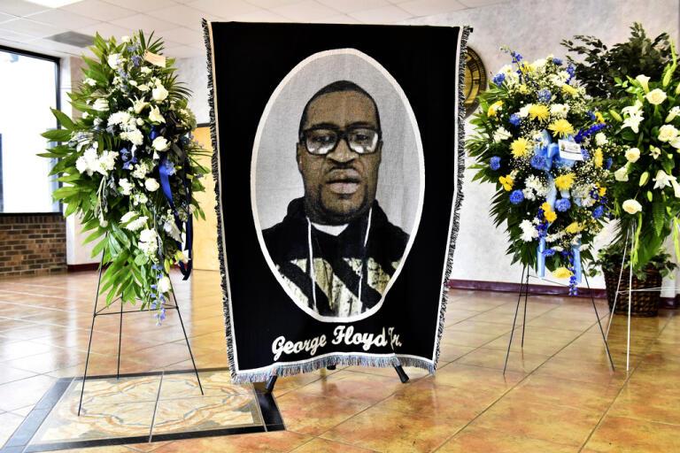 En bild på f George Floyd omgiven av blommor hade satts upp inför lördagens minnesstund i North Carolina, den delstat där Floyd föddes.