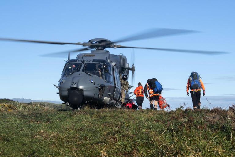 Räddningsarbetare går ombord en helikopter som användes i sökarbetet efter de två försvunna vandrarna.