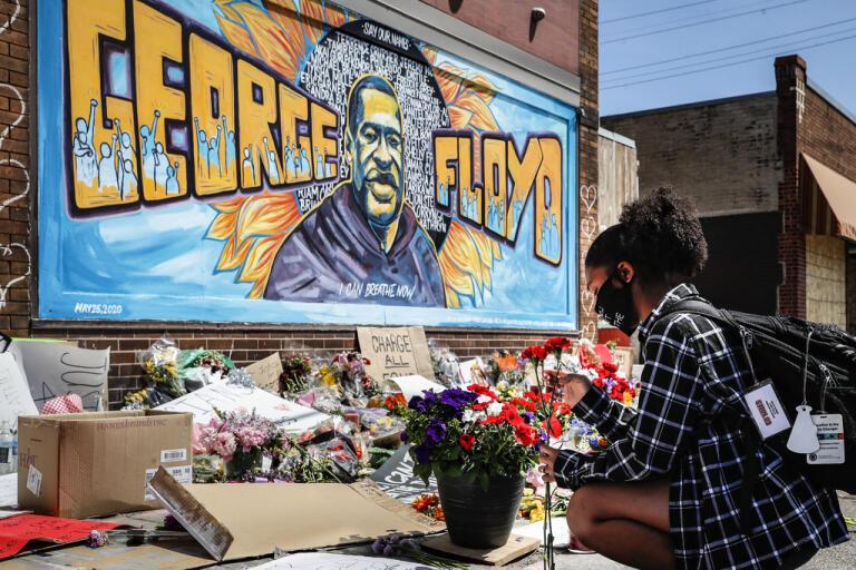 En ung kvinna lägger ner blommor framför en muralmålning av George Floyd i Minneapolis där han dog i samband med ett polisingripande. Många världsledare fördömer händelserna kring Floyds död.