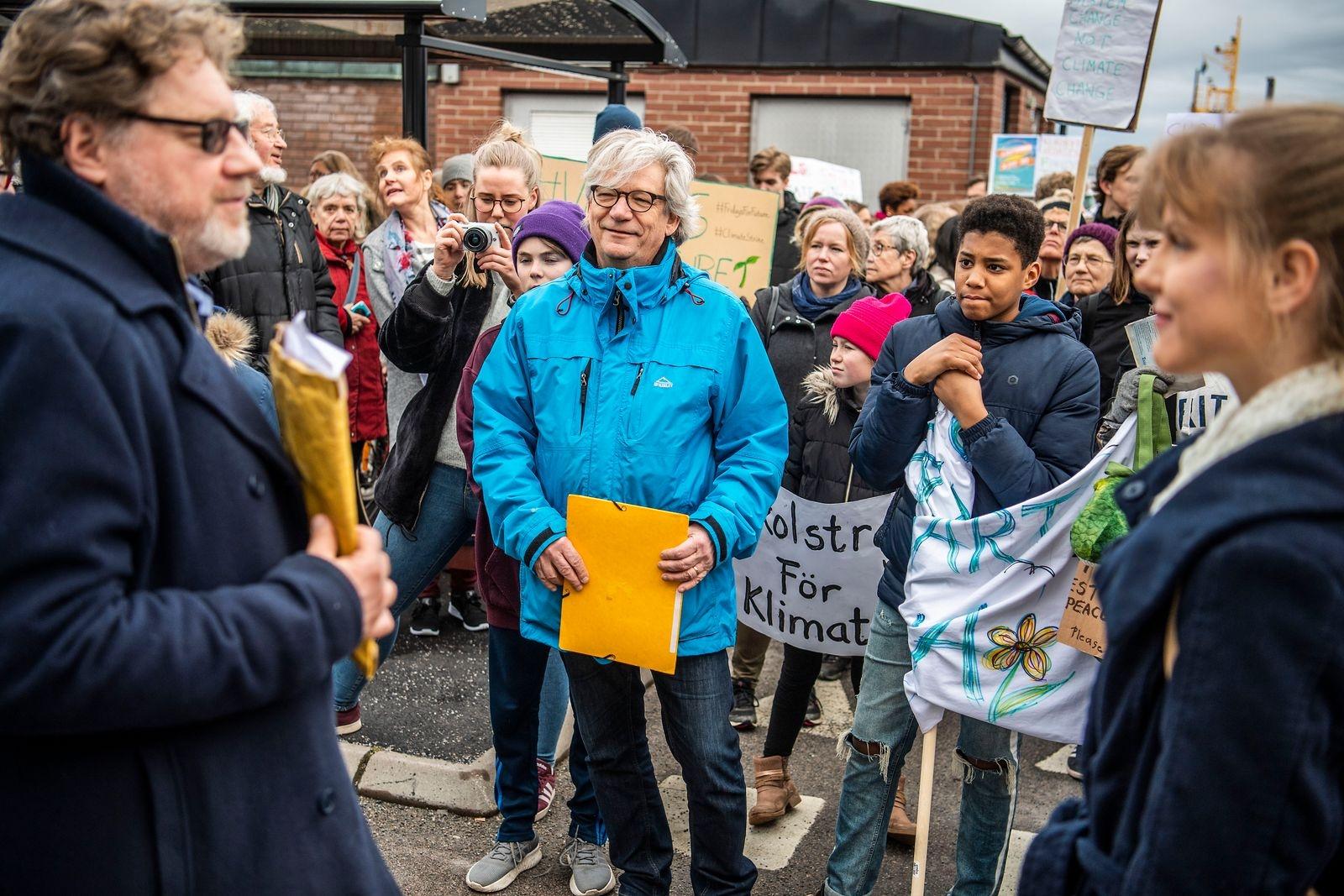 En av initiativtagarna till Fridays for future Karlskrona, Annie Karlsson, lämnar över medborgarförslaget och 350 namnunderskrifter till Magnus Larsson (C).