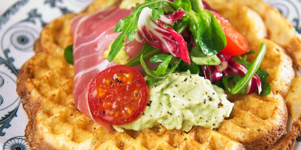 A waffle with ham, mashed avocado and lettuce.