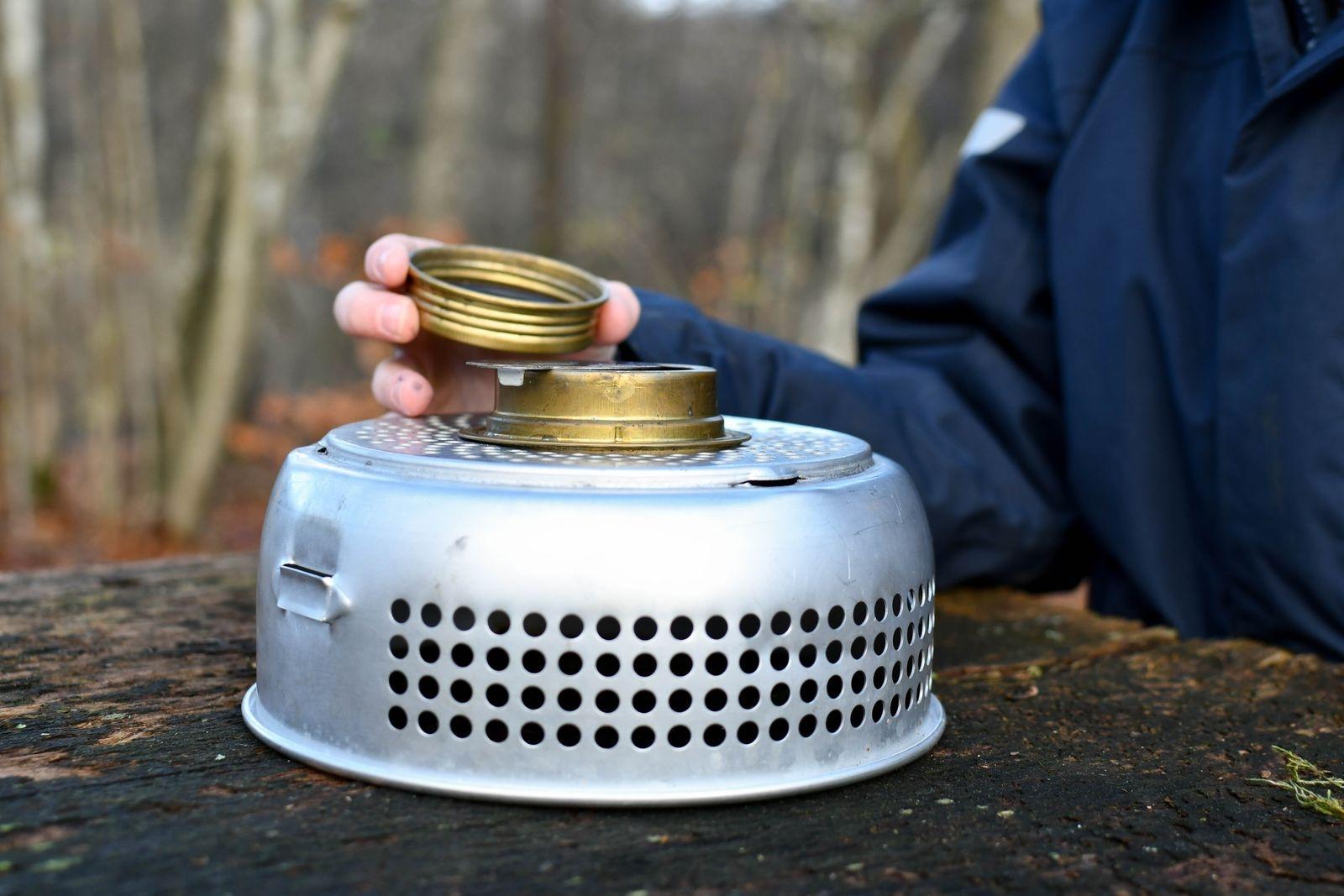 """Sätt brännaren på plats i det undre vindskyddet. Ett så kallat """"spritkök"""" drivs med Tenol eller T-röd. En fyllning av spritbrännaren (max 2/3-delar av höjden) brinner cirka 25 minuter. Fyll aldrig på bränsle i en het brännare, låt svalna innan påfyllning."""