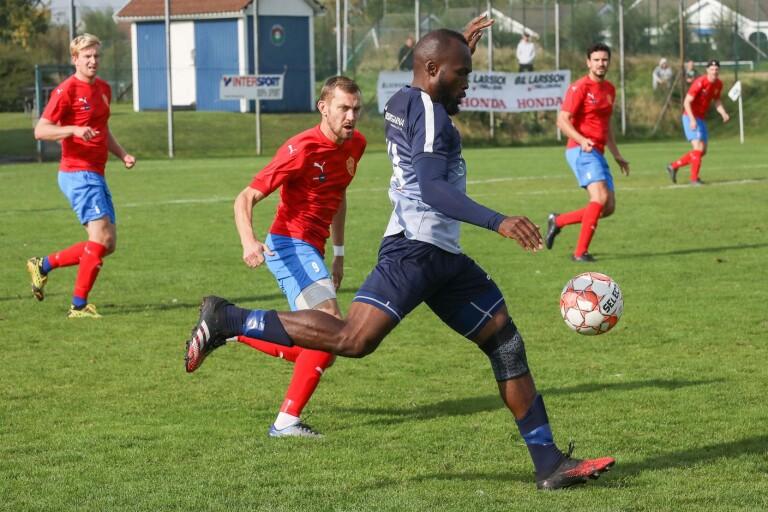 FC Trelleborgs spelande tränare Chimezie Ojiego tar sig fram mot rödklädda BK Flagg.