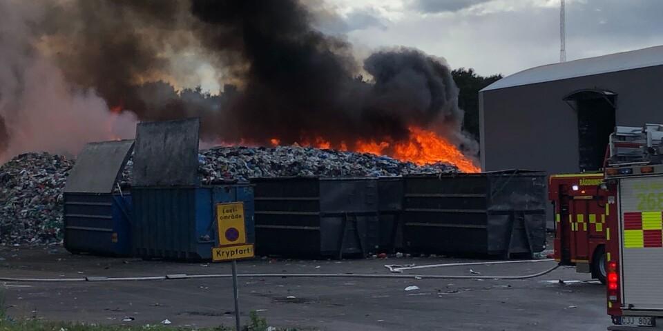 En hög med ett par tusen kubik brännbart material i brinner på Moskogens avfallsanläggning. Det finns viss risk för att branden ska sprida sig till byggnaden man ser till höger.