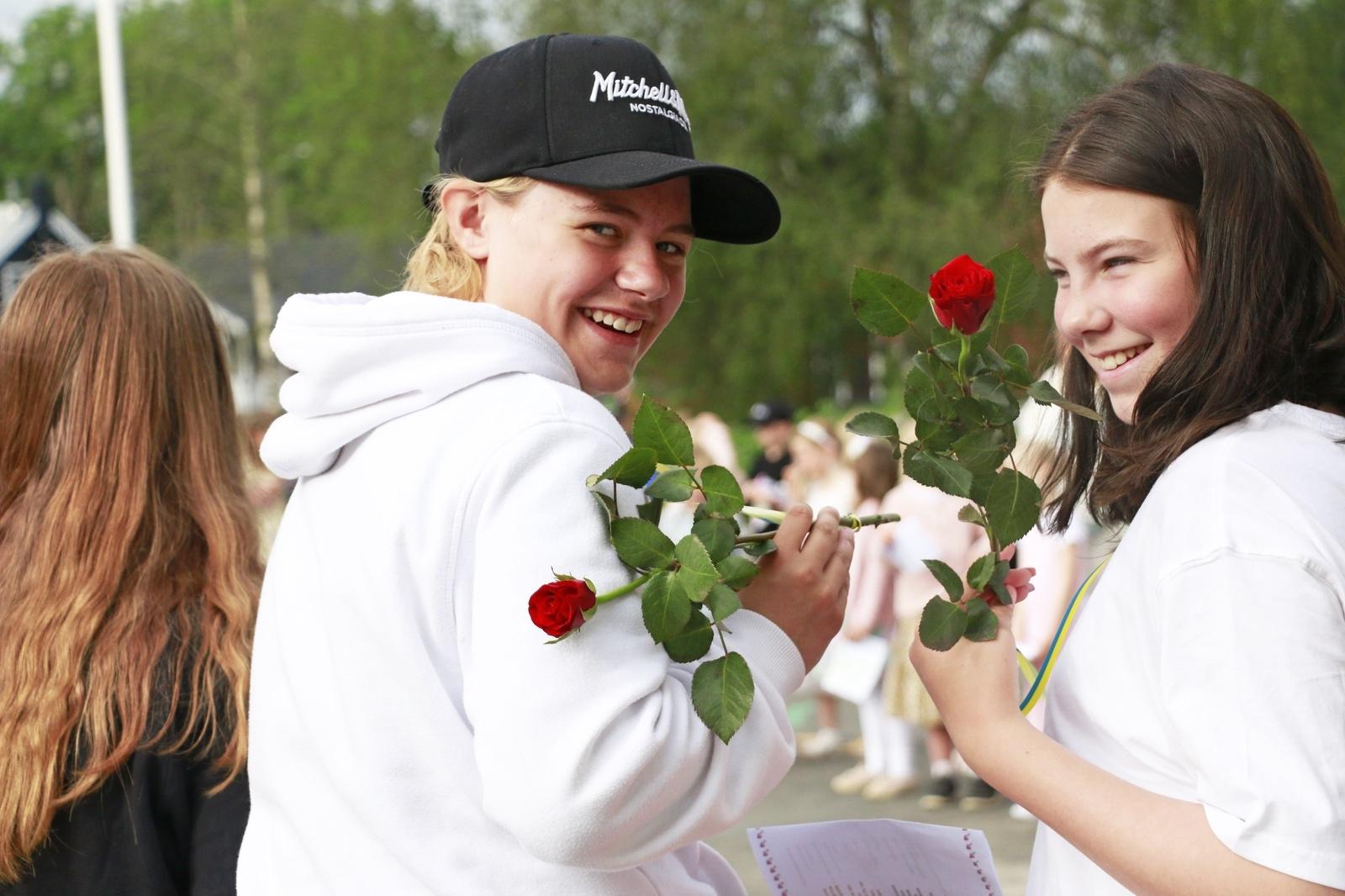 Sjätteklassarna Tindra Hulander och Mirella Johansson visar upp sina rosor.