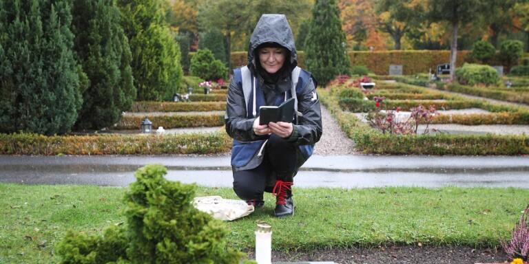 Maxine Rundgren fotograferar en grav för att skicka till en person som beställt hjälp med ljuständning på en anhörigs grav.