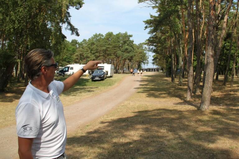 Campings ägare Anders Jonsson pekar ut platsen där de nya stugorna ska byggas.