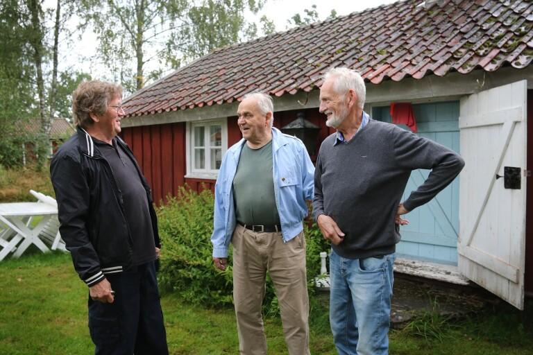 Rolf Johansson, Gustav Johansson och Wilhelm Josefsson från Vegby hembygdsförening, berättar om samhällets historia utanför en av stugorna på hembygdsgården i Vegby.
