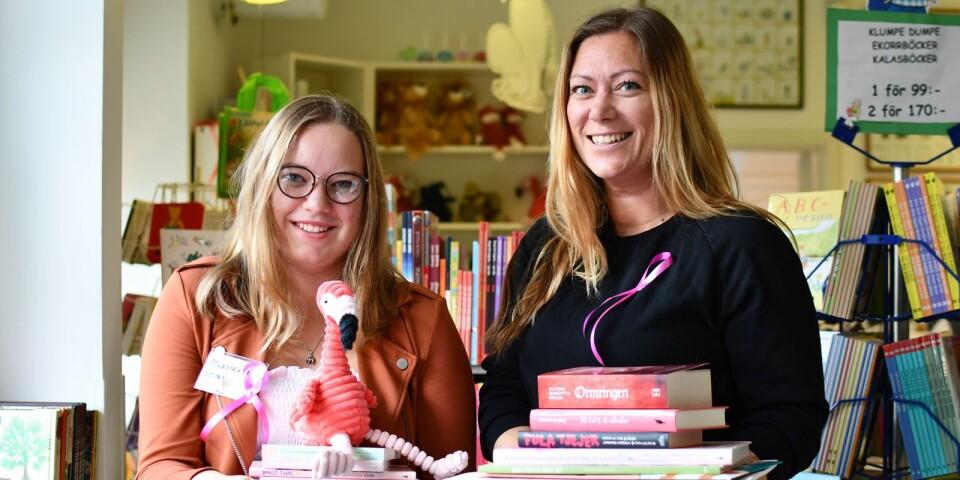 Selma Kristiansson hjälper Hanna Ottersten att, under sin praktik på Barnens bokhandel, pynta skyltfönstret på det rosa temat.