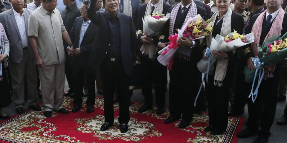 Passagerare välkomnades med blommor av Kambodjas premiärminister Hun Sen (vinkande i mitten) i Sihanoukville.