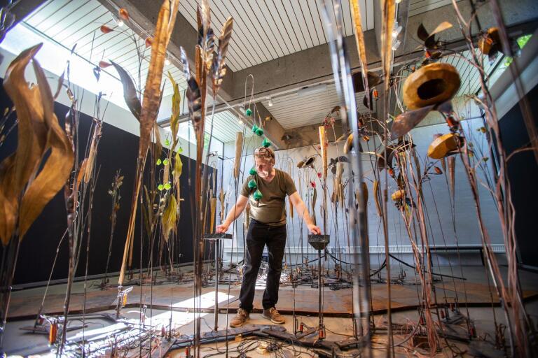 """Konstnären, musikern och ingenjören Jan Cardell justerar sin elektromekaniska, interaktiva utställning """"The Garden"""" på Trelleborgs museum."""