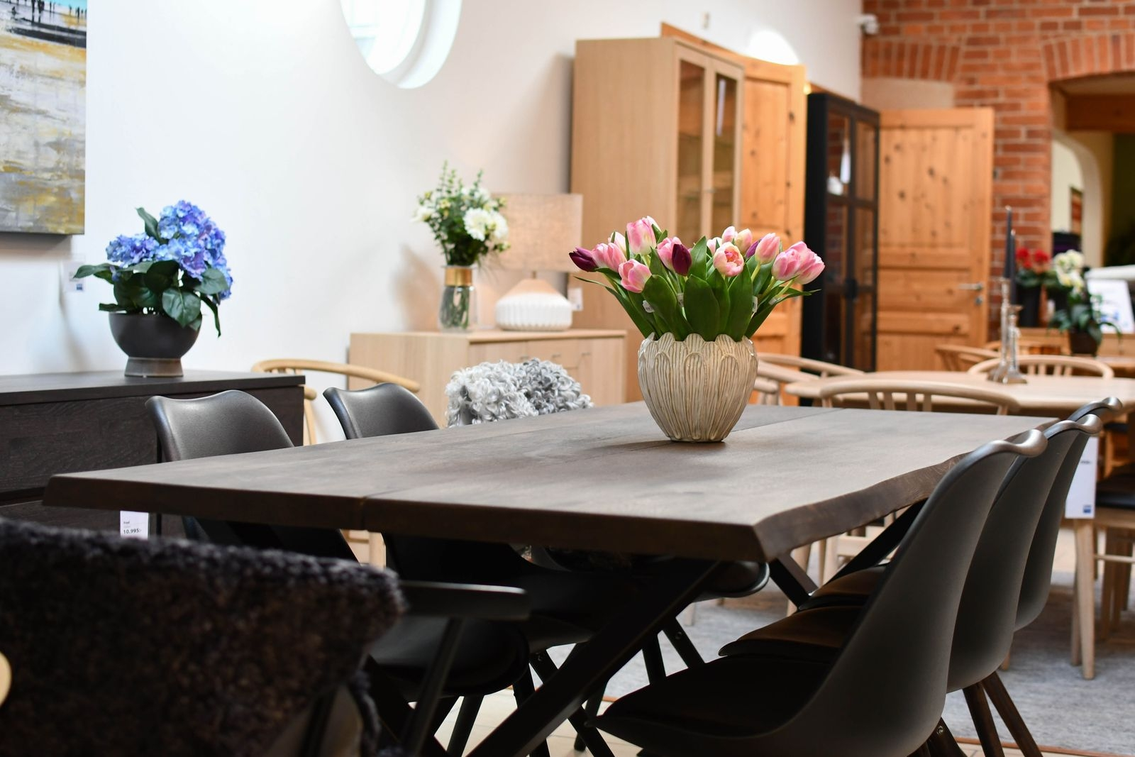 Ett matbord av brunoljad ek, med naturliga kanter och metallunderrede sammanfattar flera av vårens inredningstrender.
