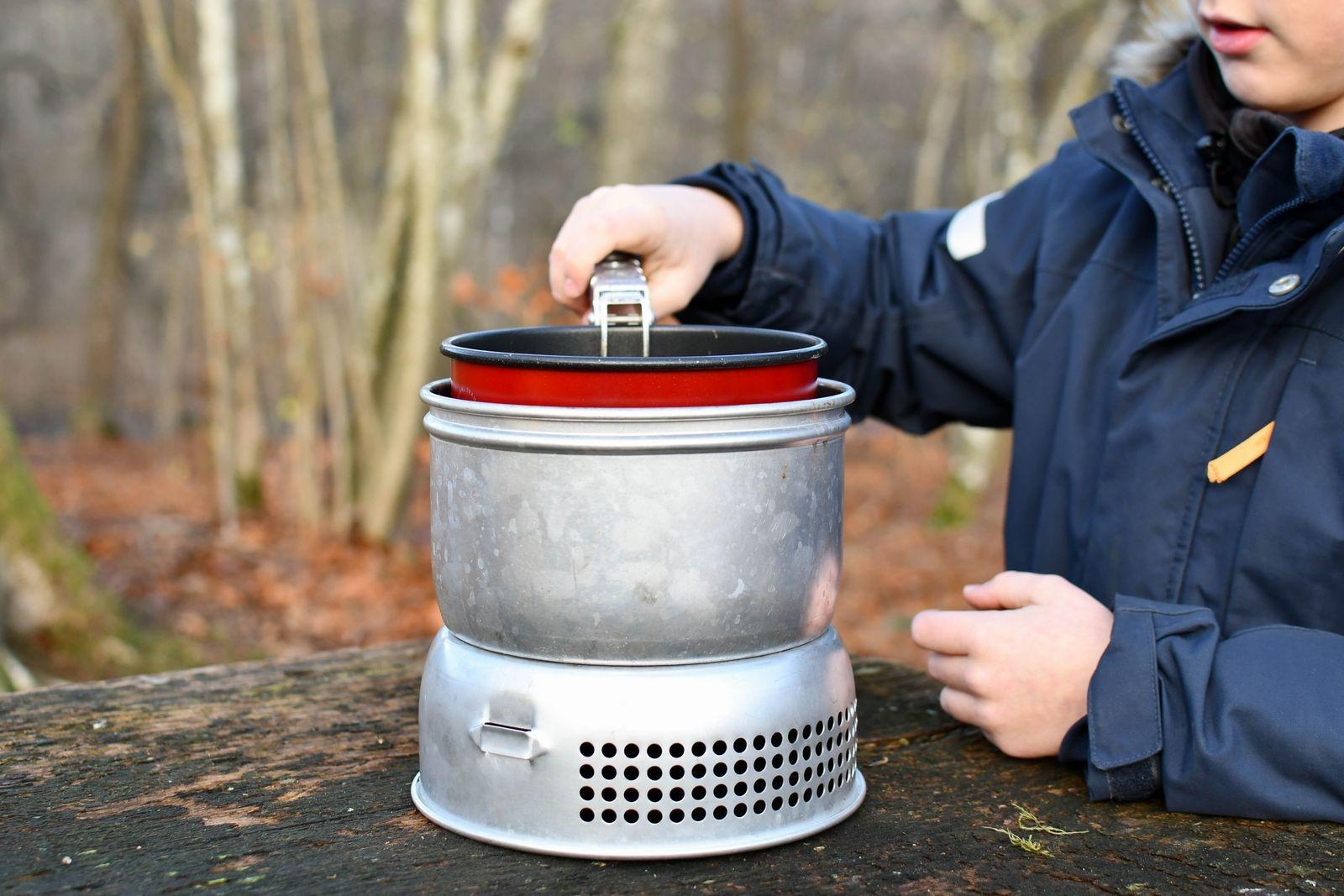 Tänd köket innan du sätter det övre vindskyddet på plats. Använder du kokkärl ställer du det på hållarna, nedsänkt i det övre vindskyddet.