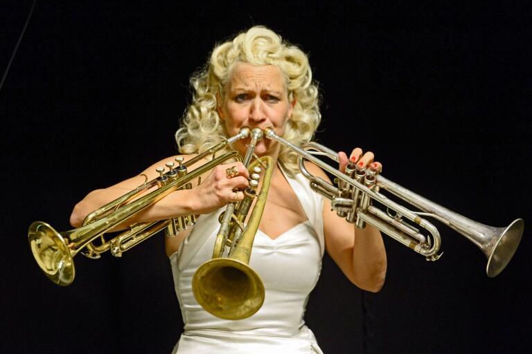 Gunhild Carling och ett av hennes specialtrick, att spela i tre trumpeter samtidigt.