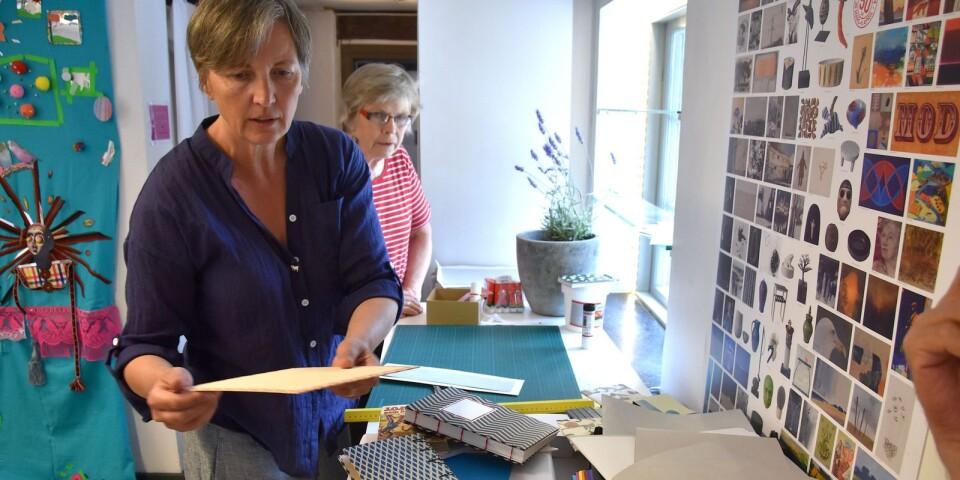 Silversmeden Lisa Tofft är också en skicklig bokbindare. Här visar hon sina kunskaper, medan kursdeltagaren Elisabeth Dahlqvist nyfiket tittar på.