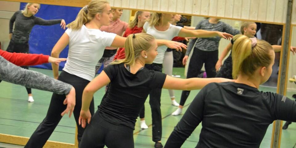 Maja Johansson, i vitt, drillar träningsgruppen med gymnasietjejer inför kommande utmaning. En föreställning inspirerad av cirkus och med rätt värdegrund.