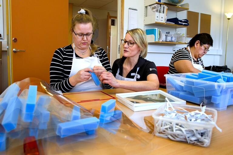 Kristina Svensson får hjälp av Emma Blomqvist. Elsa Eriksson arbetar också med att sätta ihop visir.