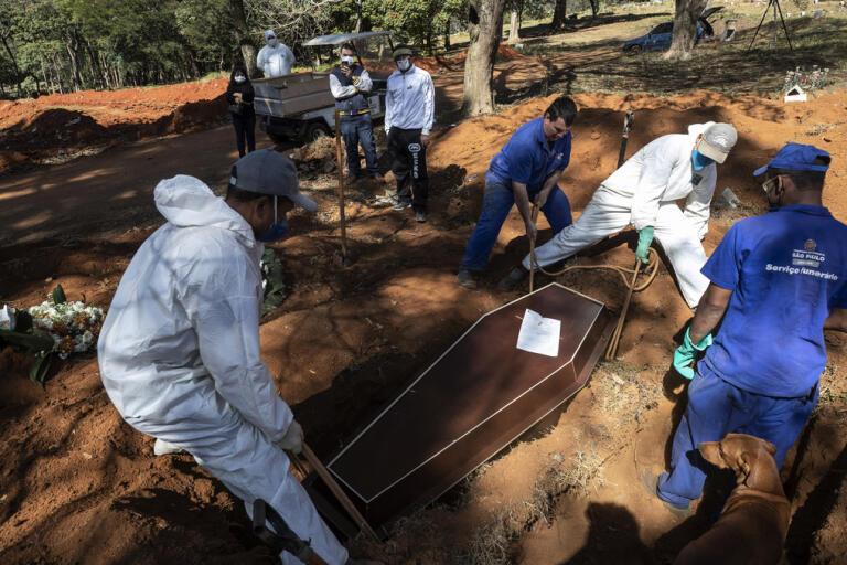 Kyrkogårdsarbetare begraver människor som avlidit till följd av covid-19 i São Paulo i Brasilien.