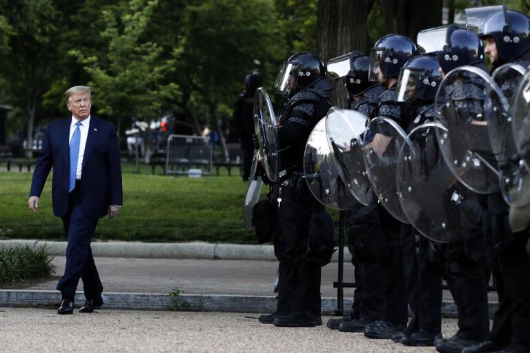 President Donald Trump passerar kravallutrustad polis i Lafayetteparken bredvid Vita huset.