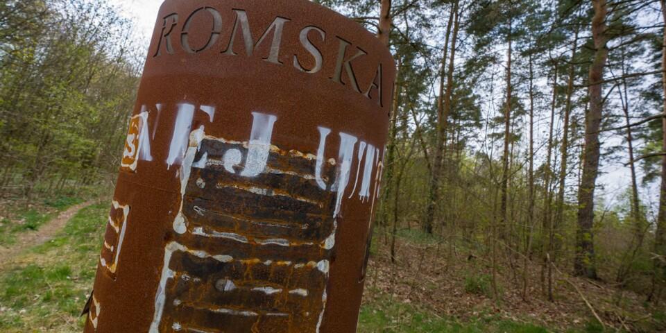 """Texten """"Nej ut!"""" har klottrats över minnesmärket vid Skräbeån i Bromölla och bilderna som berättar om romernas historia har brutits loss."""
