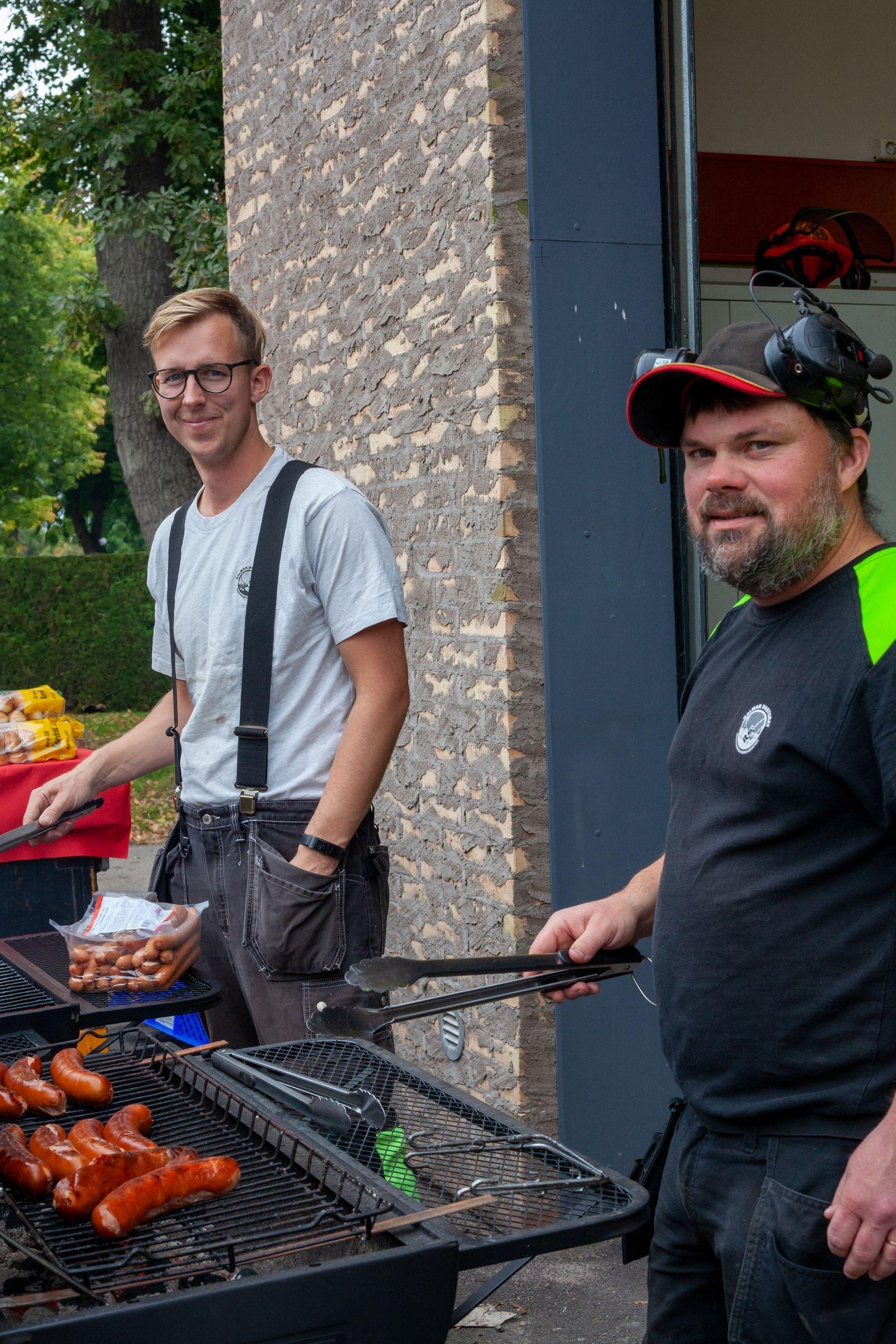 Rasmus Arréhn och Agge Tordsson som till vardags är vaktmästare/grävmaskinister vid Kalmar pastorat var grillmästare på mässan och bjöd besökare på korv.