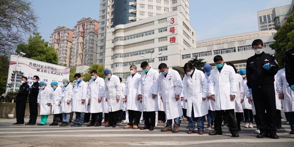 Sjukvårdspersonal i Wuhan under lördagens minnesstund.