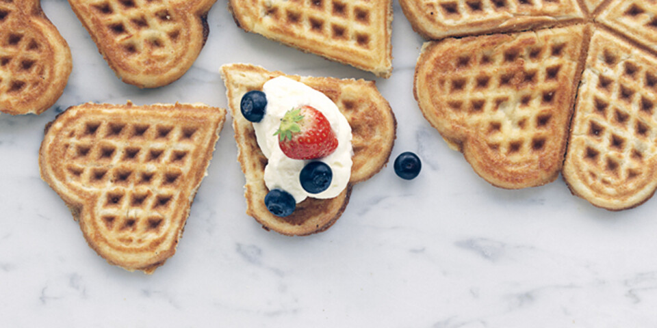 Heart-shaped waffles, with fresh bilberries, strawberries and ice-cream.