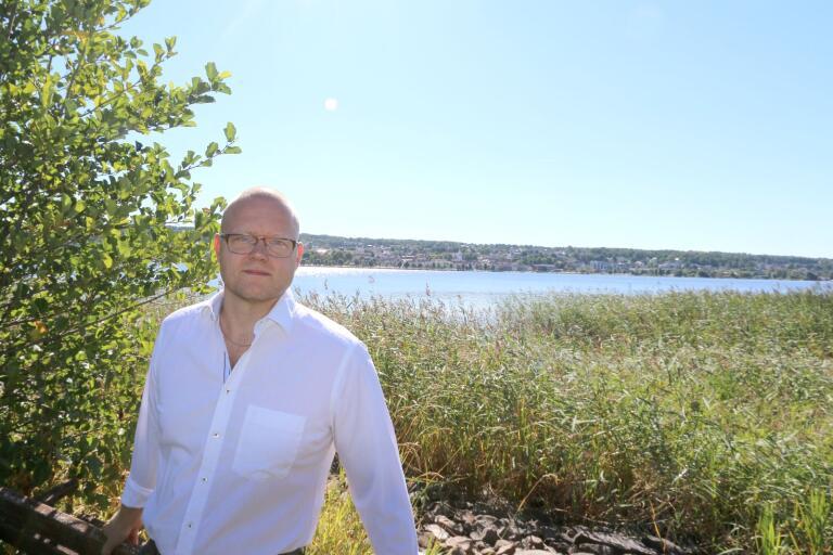 Mattias Josefsson (S) är fotograferad på stranden vid Villastaden/Båtbyggeriet i Ulricehamn. Tvärs över sjön ser man hela staden och stranden är hans barndomsstrand, då farfar byggde huset han bor i.