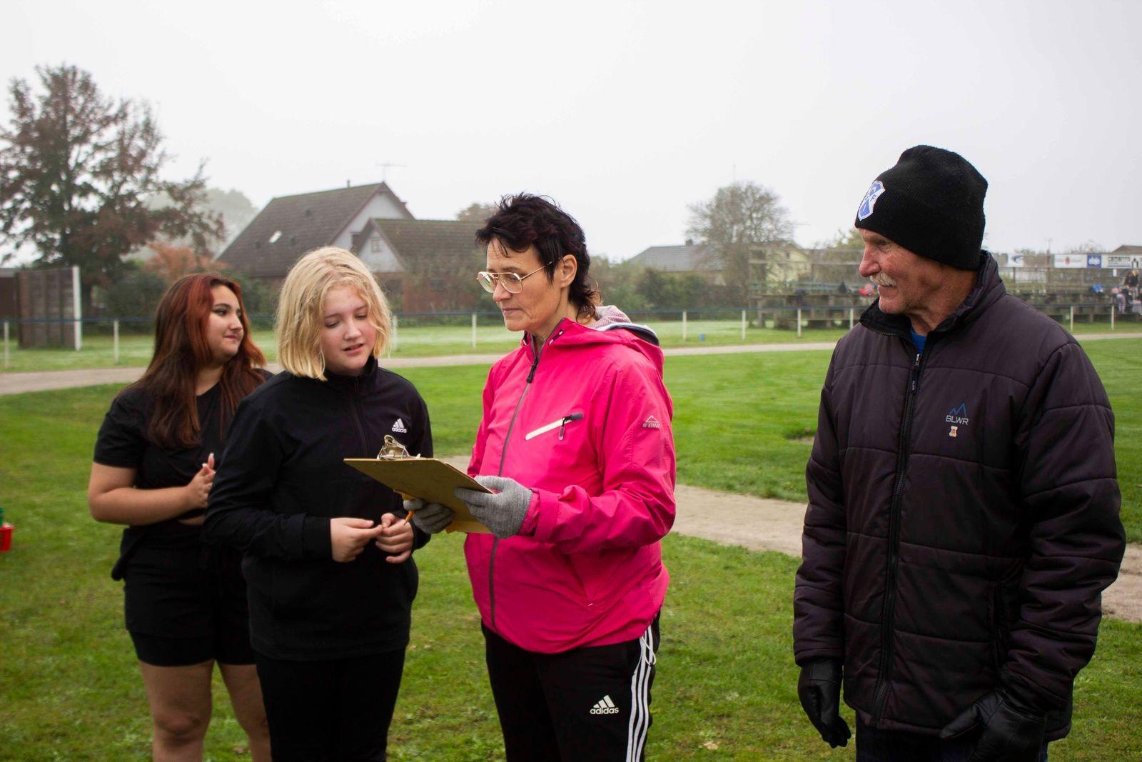 Tina Hörlin i rosa jacka visar resultatet för kulkastningen.