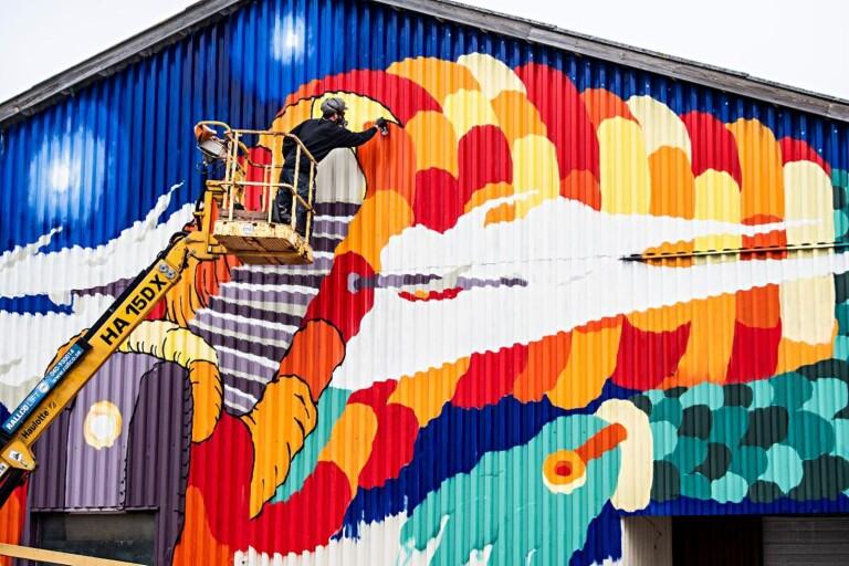 """""""Oavsett i vilken kommun man bor, bör det finnas en levande konstscen."""" På bilden: Konstnären Kim Demåne  vid sin gigantiska graffitimålning i Handelshamnen på Trossö."""