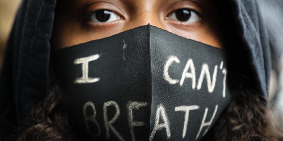 """En flicka med munskydd under en Black Lives Matter-demonstration i London. På munskyddet står det """"jag kan inte andas"""" – de ord den svarte amerikanen George Floyd sa när en polisman tryckte sitt knä mot hans nacke. Floyd avled kort därpå."""