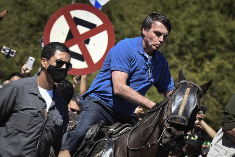 Brasiliens president Jair Bolsonaro ridande på en polishäst vid en protest utanför presidentpalatset i huvudstaden Brasília på söndagen.