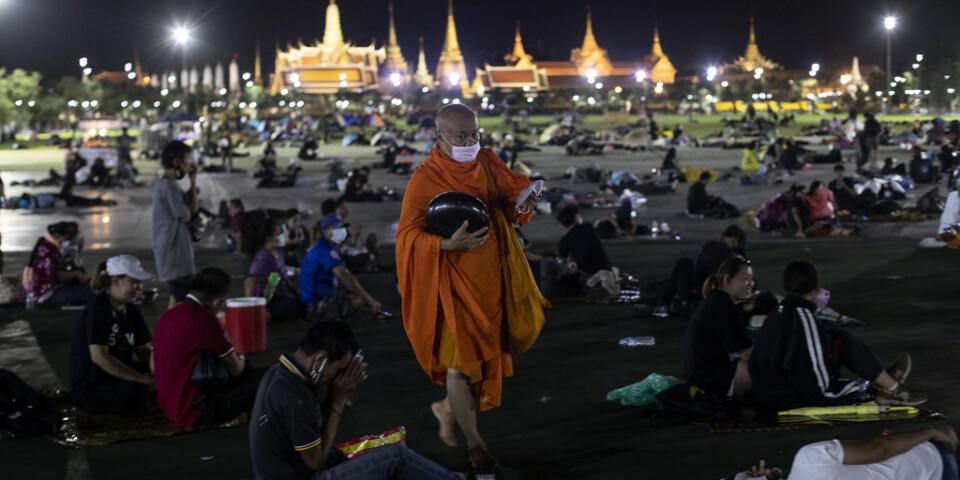 En buddhistmunk delar ut munskydd till de tusentals demonstranter som vägrade lämna Sanam Luang-torget, utanför det kungliga palatset i Bangkok, under natten till söndag.
