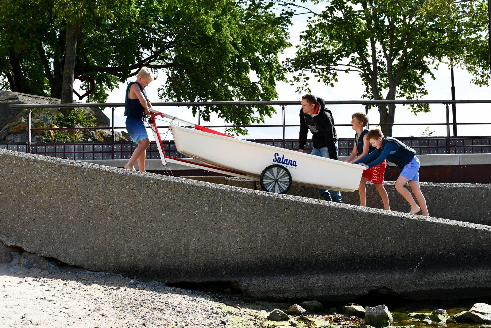 – Roligast med seglarskolan är att åka fort och att kapsejsa, säger Loke Henriksson som får hjälp av sina kompisar att ta upp jollen på land efter ett blåsigt pass.